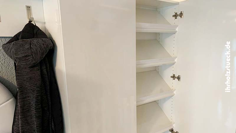 Der Garderobenschrank weiß mit Kleidungsstücken an den Haken.